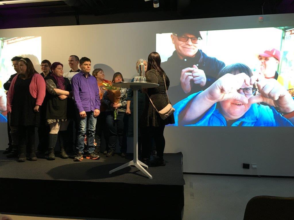 Anpassad IT vann Arvsfondens guldkorn 2018. Deltagarna på scen medan en film visas om projektet.