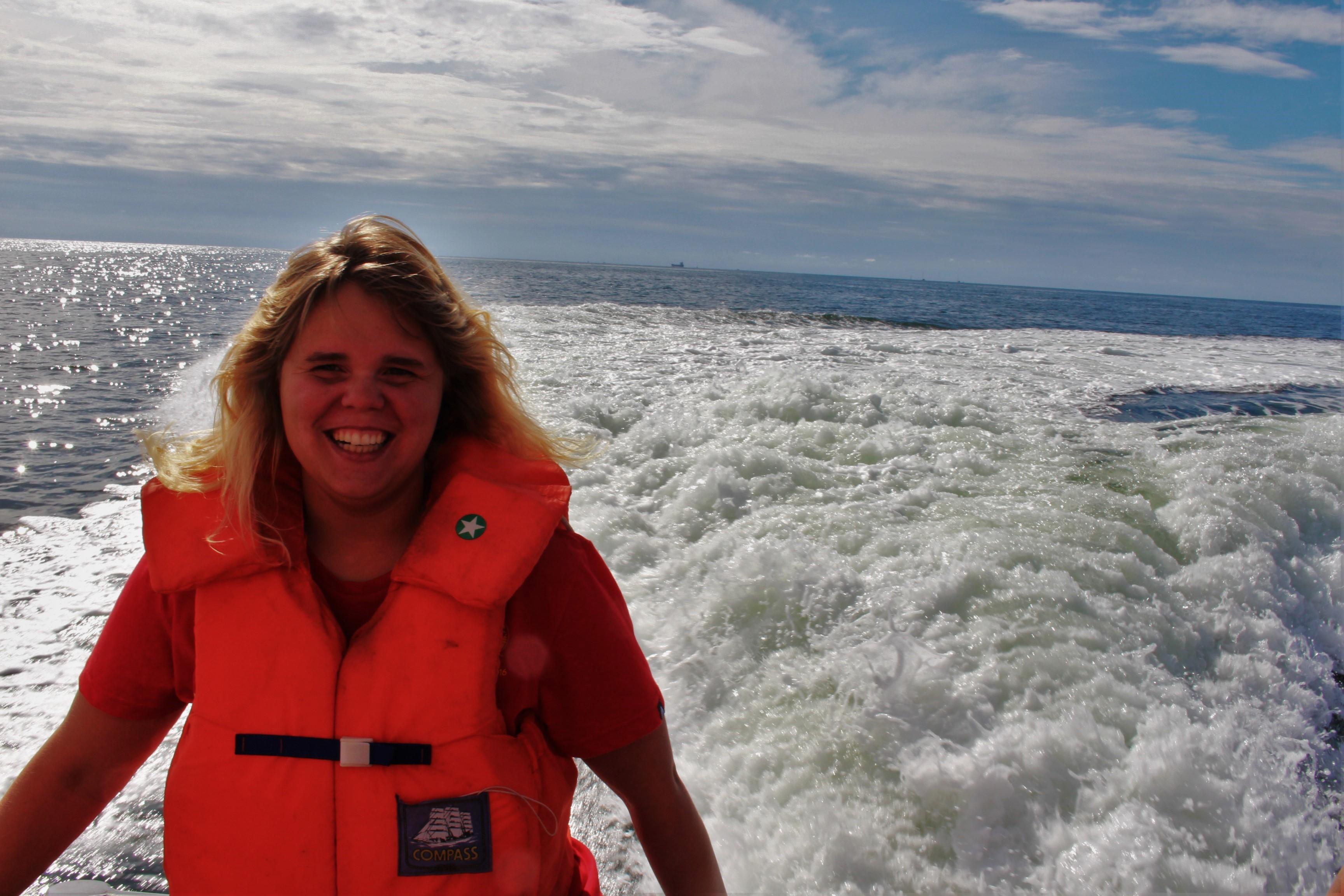 Olivia står och njuter i solen på båten