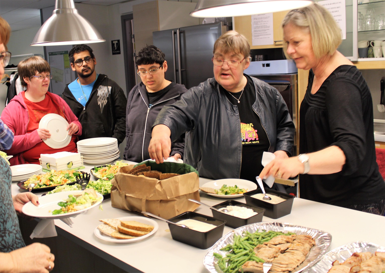 Medlemmar som står i kö till maten